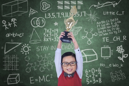 Happy boy raising trophy in classroom photo