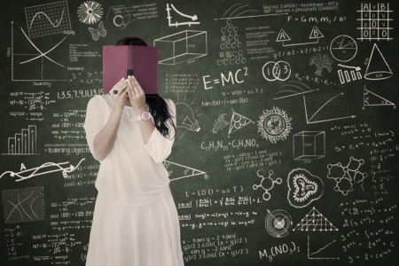 Female student is hiding behind her book in classroom Stock Photo