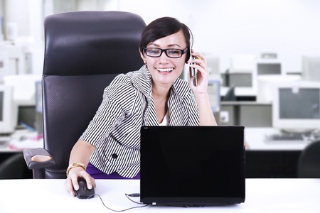 Happy businesswoman talking on the phone in office photo