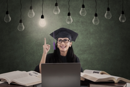 Happy female graduate has idea using her laptop under lit bulb and unlit bulbs