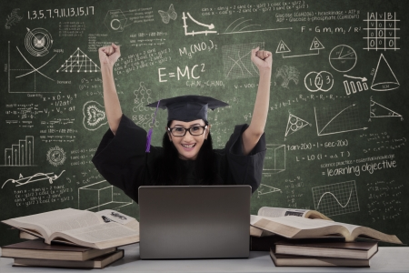 Happy female graduate raised hands using laptop in class photo