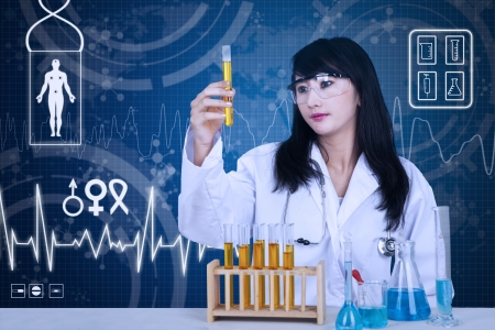 Beautiful doctor examining yellow solutions inside tubes on blue background photo