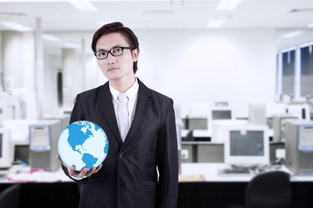 environmental suit: Confident asian businessman holding a globe in the office Stock Photo