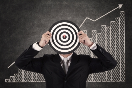 Businessman with a dart in bull's eye with written profit bar chart photo