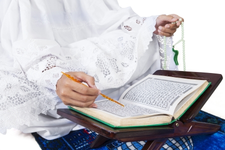 Close-up female muslim reading Quran on white background photo