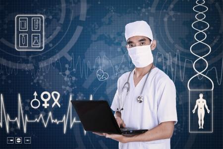man using laptop: Doctor holding laptop on digital blue background Stock Photo