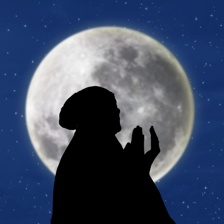 islamic pray: Silhouette of female muslim on blue moon background