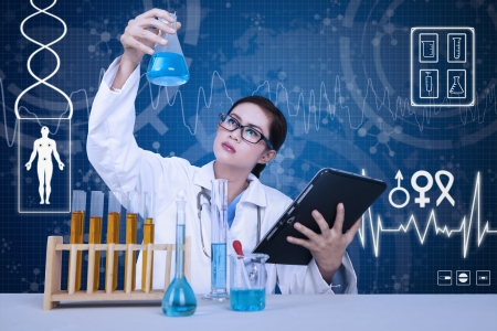 Beautiful female scientist analysing solution on blue background photo