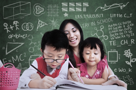 Close-up of teacher and children writing in classroom photo