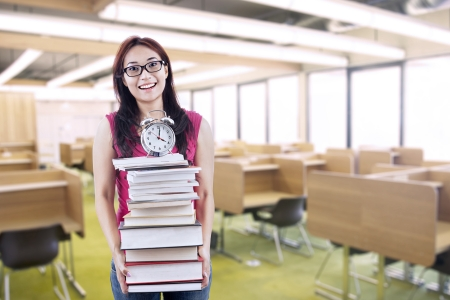 test deadline: Happy female student bring stack of books and clock in library Stock Photo