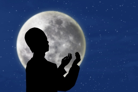 iftar: Silhouette of muslim man praying under blue moon and stars background Stock Photo