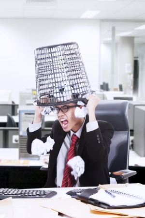 screaming head: Angry businessman screaming while hold rubbish bin on his head in the office