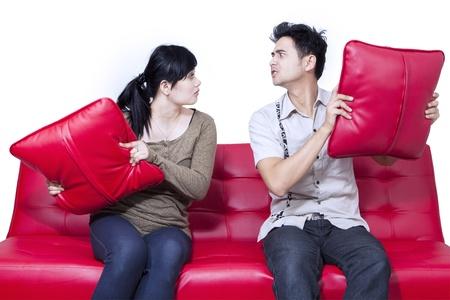 pareja enojada: Pelea de pareja asiática en el sofá aislado más de blanco