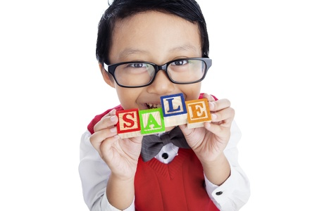 Asian boy is holding SALE wooden alphabet toy, isolated on white photo