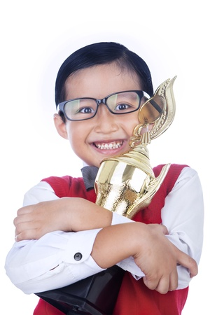 Asian boy is hugging a trophy, isolated on white photo