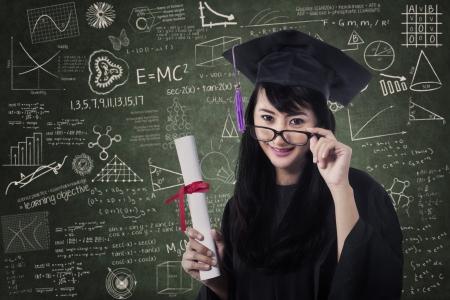 graduate asian: Asian female graduate celebrating in class with certificate Stock Photo