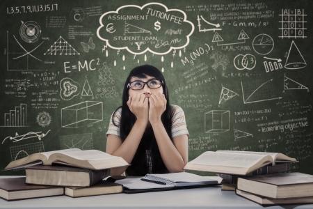美しい女性学生は教室で試験を心配します。 写真素材