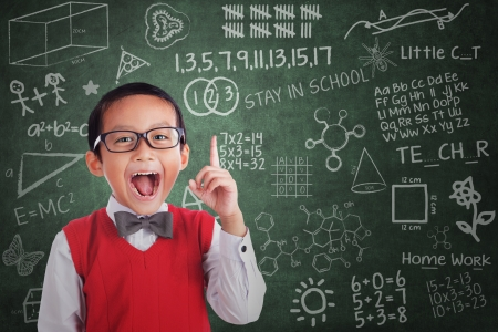 Cheerful boy student has idea in classroom