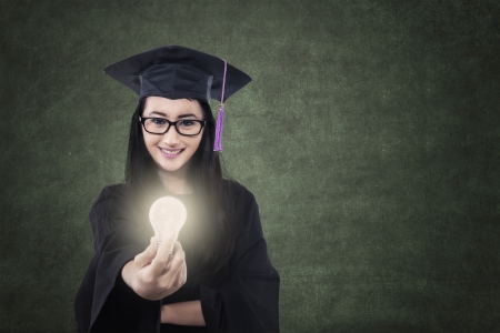 Attractive female graduate is giving lit bulb in classroom with blank blackboard photo