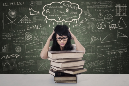 examination stress: Beautiful female stressing out due to exam with pile of books in class Stock Photo