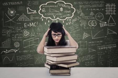 Mooie vrouwelijke belasting te wijten aan examen met een stapel boeken in de klas Stockfoto