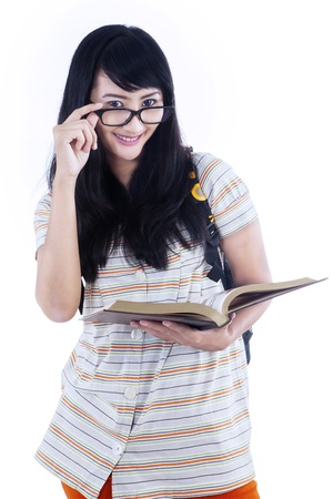 Attractive female student is looking at camera while holding book on white Stock Photo - 20726167
