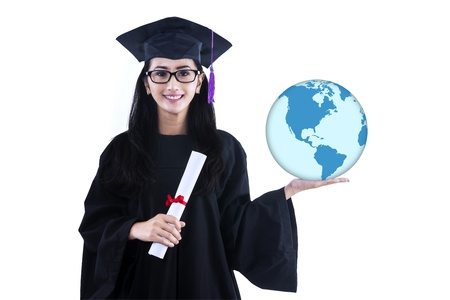 Beautiful young female graduate holding world globe on white background photo