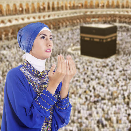 Beautiful muslim woman praying at Kaaba, Mecca, Saudi Arabia photo