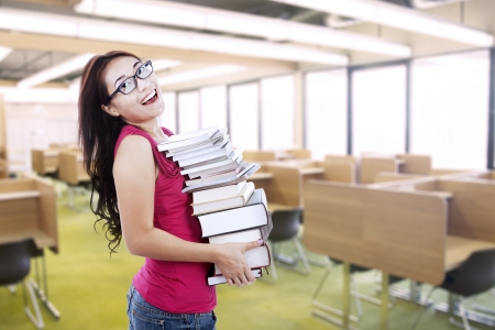 education loan: Beautiful Asian student bring stack of books indoor