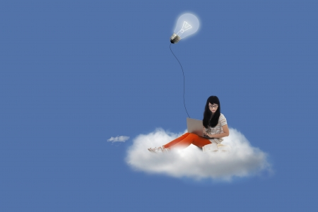 Beautiful woman sitting on cloud using laptop under lightbulb Stock Photo - 20726257