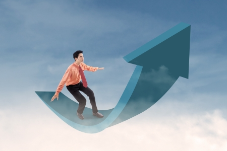Businessman is standing on up arrow sign in the sky photo