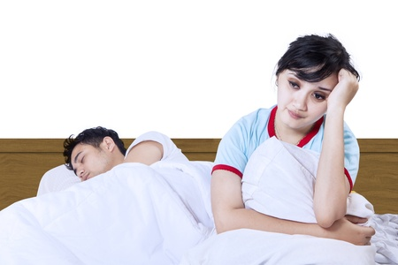 Asian wife having insomnia while her husband asleep on bed