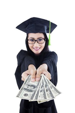 rewarding: Asian female graduate is holding money on white background