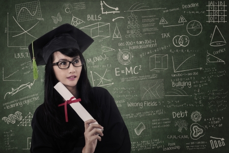 Attractive nerd female graduate wearing gown at class photo