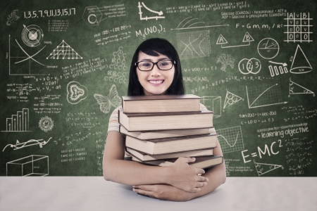 Young asian college student with books in class photo