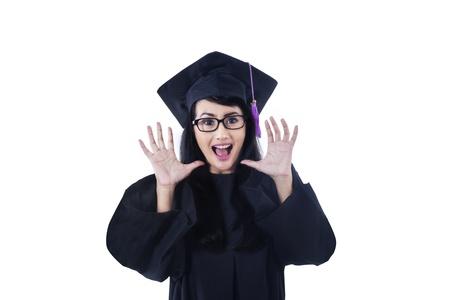 graduacion de universidad: Graduado femenino emocionada que grita en el fondo blanco Foto de archivo