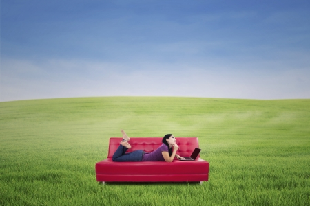 red sofa: Thoughtful young woman lying on couch with laptop - shot on the spring meadow