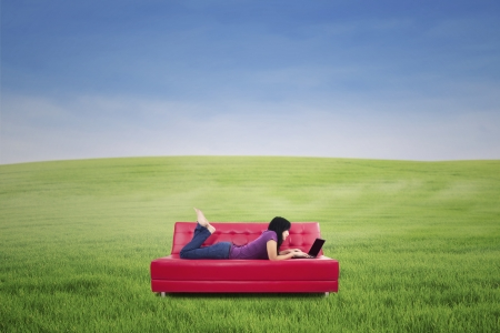 Girl lying on couch with a laptop on the spring meadow photo