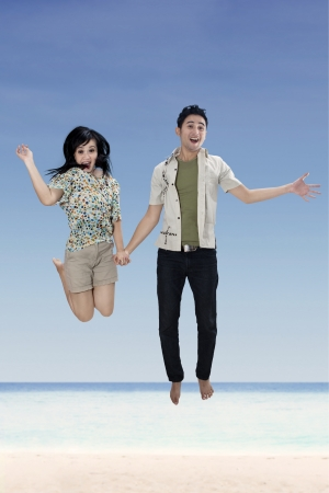 Young couple jumping on the white sand beach photo