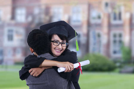 Happy woman is hugging boyfriend on graduation day outdoor photo