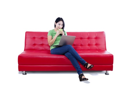 red sofa: Asian female is having coffee while sitting on red sofa with laptop on white background