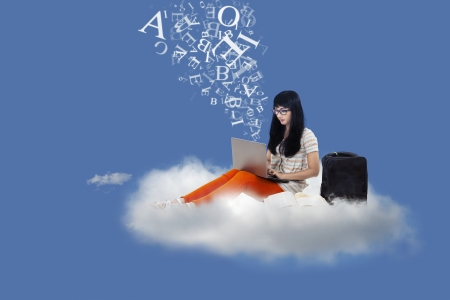 libros volando: Hermosa estudiante sentado en una nube bajo el cielo azul con el portátil y cartas de vuelo Foto de archivo