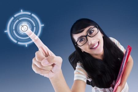 Retrato de una joven atractiva estudiante universitaria tocar la pantalla virtual Foto de archivo