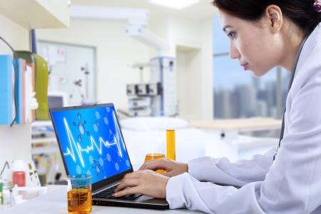 laboratorio clinico: Doctora atractivo trabajar con el portátil en el laboratorio