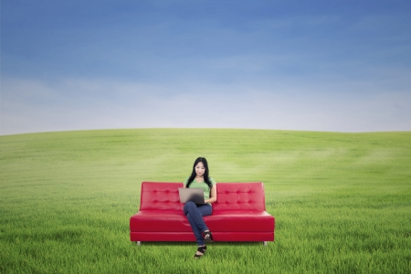 Beautiful woman sitting on red sofa while working online outdoor Stock Photo - 20772824