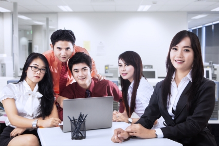 Group of friendly businesspeople with happy female leader in front photo