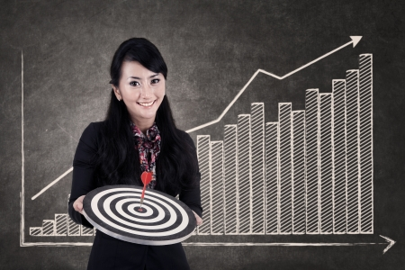 Businesswoman hold bull's eye on growing bar chart chalkboard as the background photo