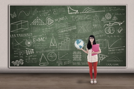 Young asian student holding globe in front of class with formula on blackboard photo