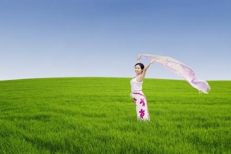 aire puro: Mujer asiática joven que disfruta de la libertad por el pareo en la pradera