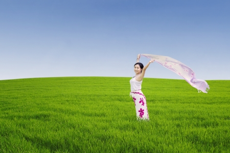 breath: Young asian woman enjoying freedom by sarong on the meadow Stock Photo
